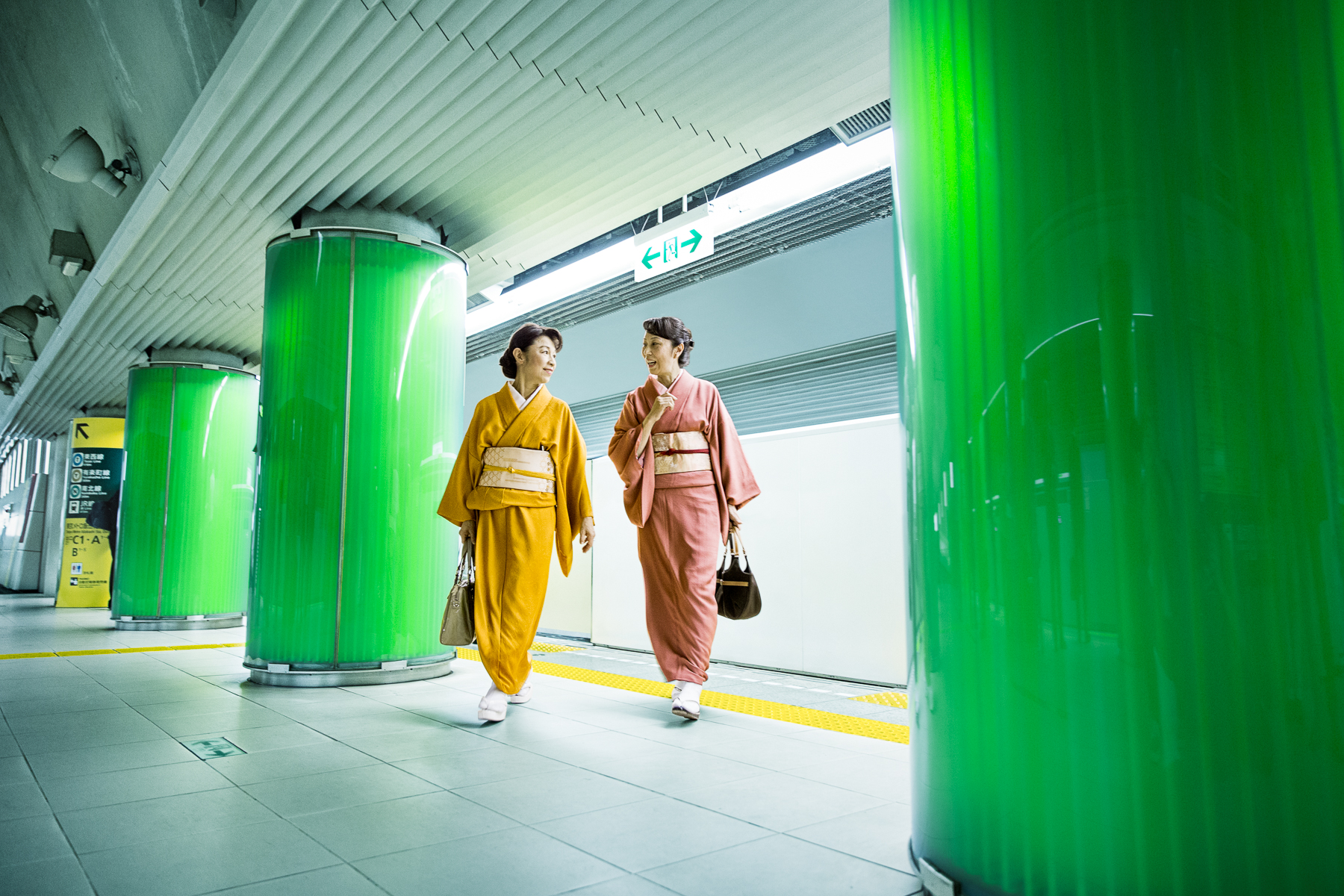 Two Women in Kimonos Walking  in a Subway Station